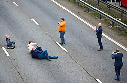 © Licensed to London News Pictures. 19/09/2017. HANSLOPE, UK. A group of men on the tarmac of an empty section of motorway on the closed carriageway of the M1 near Hanslope between junctions 15 and 14. The road has been closed since 7:30am this morning, trapping hundreds of people, as the police deal with a suspicious item found under a bridge. The location is very near to Hanslope Park, home to Her Majesty's Government Communication Office (HMGCC0, part of FCO.  Photo credit: Cliff Hide/LNP