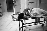 A woman in pain on a stretcher has contractions and waits to have a Caesarian section performed. Qatar hospital, Orangi town, Karachi, Pakistan 2010