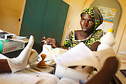 Midwife Zeynabou Haidara explains documents to Fanta Kamissoko (R), 22, 6 mo pregnant as they wait for the result of her HIV test during a prenatal consultation at the Kita reference health center in the town of Kita, Mali on Monday August 30, 2010..