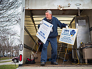 """26 MARCH 2020 - DES MOINES, IOWA: A worker unloads signs before hot lunch distribution at Weeks Middle School. Des Moines Public Schools (DMPS) started distributing hot lunches Thursday, the first day students were supposed to return to school. Schools will now remain closed until 13 April. Meals were distributed with """"social distancing"""" in mind. On Thursday morning, 24 March, Iowa reported 175 confirmed cases of the Coronavirus (SARS-CoV-2) and COVID-19. Restaurants, bars, movie theaters, places that draw crowds are closed until 07 April. The Governor has not ordered """"shelter in place""""  but several Mayors, including the Mayor of Des Moines, have asked residents to stay in their homes for all but the essential needs. People are being encouraged to practice """"social distancing"""" and many businesses are requiring or encouraging employees to telecommute.         PHOTO BY JACK KURTZ"""