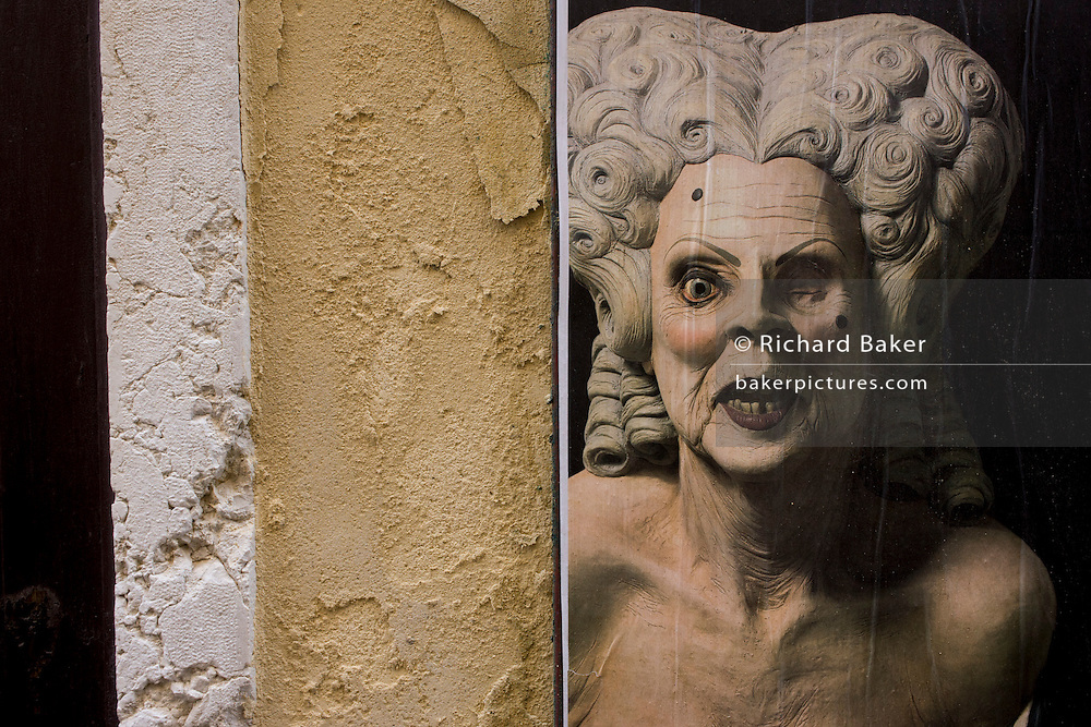 The texture of wall plaster echoed in the skin of a theatrical character in the San Marco shopping district of Venice, Italy.