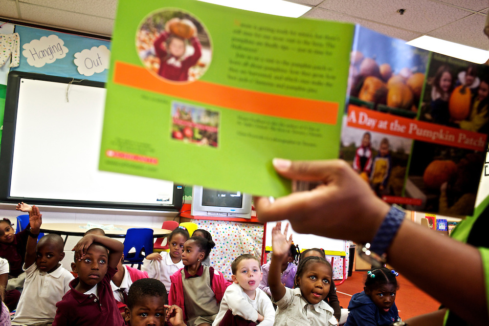"Pre-kindergarten students at Calvin Rodwell Elementary School No. 256 in Baltimore, MD, listen to their teacher Erika Parker, right, as they read the book ""A Day at the Pumpkin Patch,"" a non-fiction children's book about visiting a farm. The book was part of a ""Common Core"" reading and learning unit, which aims to follow up non-fiction reading with learning in the field. The day after the children read the book about the farm, they visited Summers Farm in Frederick, MD."