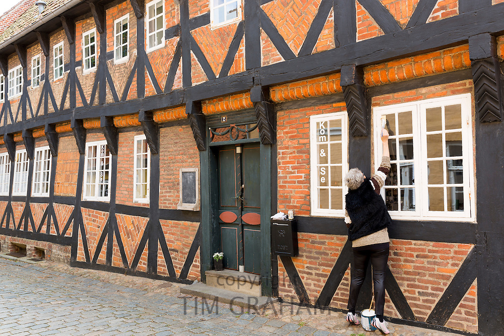 Local woman painting Kom and Se half-timbered medieval shop, Puggaardsgade and Sonderportsgade, Ribe centre, Denmark