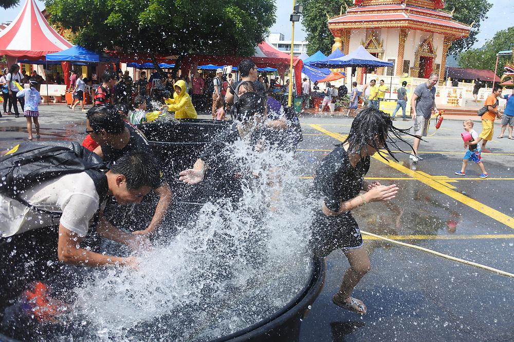 Two Guys splashing girls at the Songkran water festical in Penang