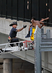 June 22, 2017 - St. Louis, MO, USA - A fireman from the St. Louis Fire Department extends a hand to assist a man down off the Compton Avenue overpass on Interstate 44 East in St. Louis on Thursday, June 22, 2017. The man was threatening to jump off the bridge on to the highway. Police shutdown Eastbound 44 for 15 minutes while the man was helped off the bridge and brought safely to the ground. (Credit Image: © David Carson/TNS via ZUMA Wire)