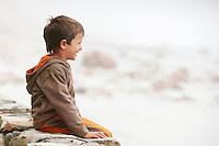 Boy (5-6) sitting on wall on beach