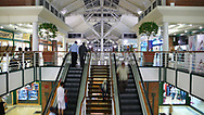 Shoppers going up and down on escalators in the Victoria Wharf Shopping Centre. Cape Town, South Africa.
