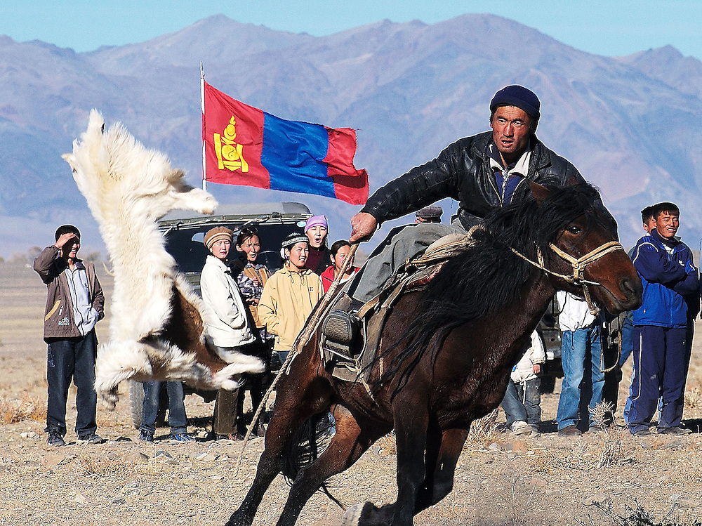 Throwing the goat skin with panache is a challenge to all other riders after winning an individual match in Kokpar also known as Bushkashi at the annual Eagle Hunting Festival, Bayan Olgi, Mongolia, Oct 6, 2003.  Kokpar requires a combination of strength, courage, and horsemanship skills.  This traditional game has come back since the Soviet withdrawal from the region.  The Kazakhs of Mongolia play one on one, with 10 men on each team.  When a rider loses his grip on the goat or falls off his horse he has to join the opposing team.  Eventually one team has all the riders on its side and is the winner.  Kokpar or Bushkashi is also played in a ruby style in other parts of Central Asia including Kazakhstan.  Hundreds of riders may line up on each side, and then mayhem prevails as they all rush to grab the goat.