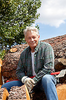 Portrait of smiling senior man sitting on logs