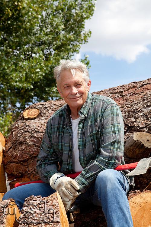 Portrait of smiling senior man sitting on logs