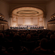 """December 12, 2012 - New York, NY : Conductor Gustavo Dudamel, on pedestal, leads the  Westminster Symphonic Choir and the Simón Bolívar Symphony Orchestra of Venezuela as they perform Heitor Villa-Lobos's """"Chôros No.10"""" at Carnegie Hall's Stern Auditorium / Perelman Stage on Tuesday evening.  CREDIT: Karsten Moran for The New York Times"""