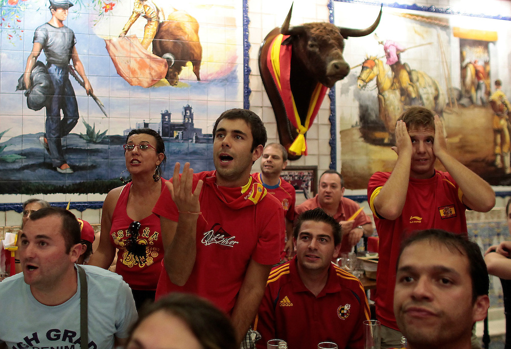 Spanish fans reacts during the final World Cup match against Netherlands in a bar decorated with bull's heads in Madrid on Sunday, July 11, 2010. Spain won 1-0.