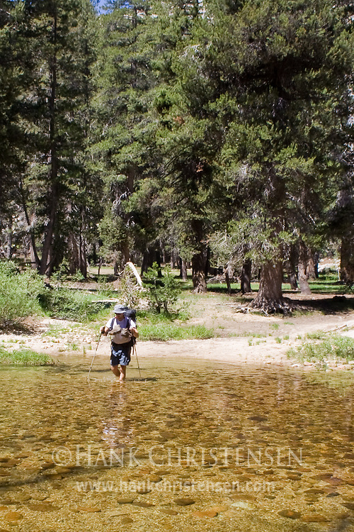Backpacker crosses a creek along the Pacific Crest Trail, Yosemite National Park