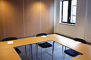 Vacant desks and empty chairs are placed facing each other for a counselling workshop held for company employees at Prospect House, Borough, Southwark, London. Soon, employees of this seminar will arrive for a day's role-playing in this classroom setting where the office furnature makes a square to force participants to confront their opposite numbers. Jotter pads are provided for brainstorming ideas and concepts that help E & Y get the best out of their talented people. The room is otherwise empty as bright daylight floods through a window allowing positive thoughts and bright ideas to influence their thinking.
