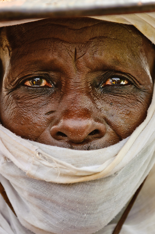 Portrait of a Fulani herdsman wearing a traditional hat and robes in northern Burkina Faso. The Fulani or Peul are nomadic herdsmen of the Sahel region of West Africa.