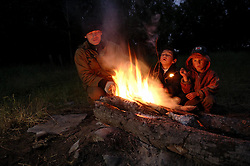 Astashov Aleksei sits by a fire with an indigenous family of Chukchu tribals waiting for them to finsih collecting salmon roe that they will sell to him along the river Vyvenka in Khailino, Kamchatka July 15, 2007. Most indigenous people rely on the salmon harvested in the summer for the whole year. They dry it and feed it to themselves and their dogs that they use to get around on sleds in the harsh winter months. Because the area is so remote and no longer subsidized by the Russian or Soviet government of the past goods and gasoline are extremely expensive. The economy is struggling and the only way for most people to survive is through poaching and fishing in the short summer months. So now the fish population is rapidly declining as poachers collect the eggs and don't allow the salmon to spawn for the next generations.