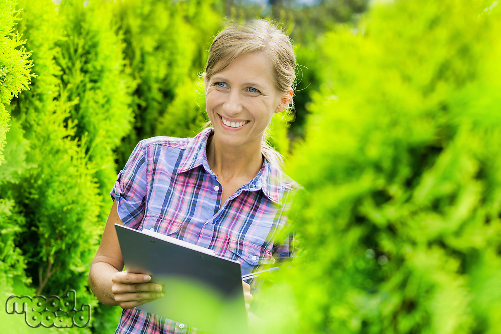 Portrait of mature owner smiling while writing report on clipboard in garden