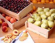 Sliced fruit on a cutting board with crates of fresh fruit in the background