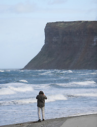© Licensed to London News Pictures. <br /> 21/10/2014. <br /> <br /> Saltburn, United Kingdom<br /> <br /> A man takes pictures of rough seas as strong winds lash the coast of Saltburn in England as the tail end of what was Hurricane Gonzalo reached the UK today causing some disruption in parts of the country.<br /> <br /> Photo credit : Ian Forsyth/LNP