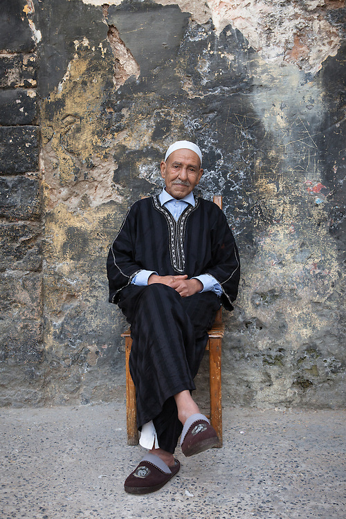 Portrait of an old muslim man, wearing a traditional black djellaba, in the old medina of El Jadida, Morocco.