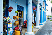 A shop assistant measures out rope at a brightly painted colonnaded style store along the Venustiano Carranza in Tlacotalpan, Veracruz, Mexico. The tiny town is painted a riot of colors and features well preserved colonial Caribbean architectural style dating from the mid-16th-century.
