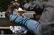 A Cowboy talks to a colleague as he stretches before competition at the Falkland Stampede in Falkland, BC (2012)