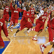 "Players from Western Kentucky University sprint onto the court at the St. Pete Times Forum Friday, after they stunned Drake University with a winning buzzer-beating 3 point shot in the NCAA Basketball Tournament Western Regional played in Tampa, Florida.  The shot, made by Ty Rogers was about 6 feet beyond the 3 point arc.  The win was another example of ""March Madness"", where upsets by lower seeded teams are common.  Drake was a 5th seed and Western Kentucky was a 12th seed."