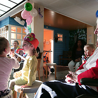 Nederland, Rijswijk , 28 oktober 2009..Kinderen en ouderen komen samen in verpleeghuis Westhoff en vieren b.v. samen verjaardagen. Het schijnt dat de aanwezigheid van kinderen psychisch een positieve invloed heeft op ouderen en dementerede ouderen in een verpleeghuis..Links op de achtergrond activiteitenbegeleider van de afdelingen van westhoff...Children and elderly meet in nursing home Westhoff and celebrate birthdays together.