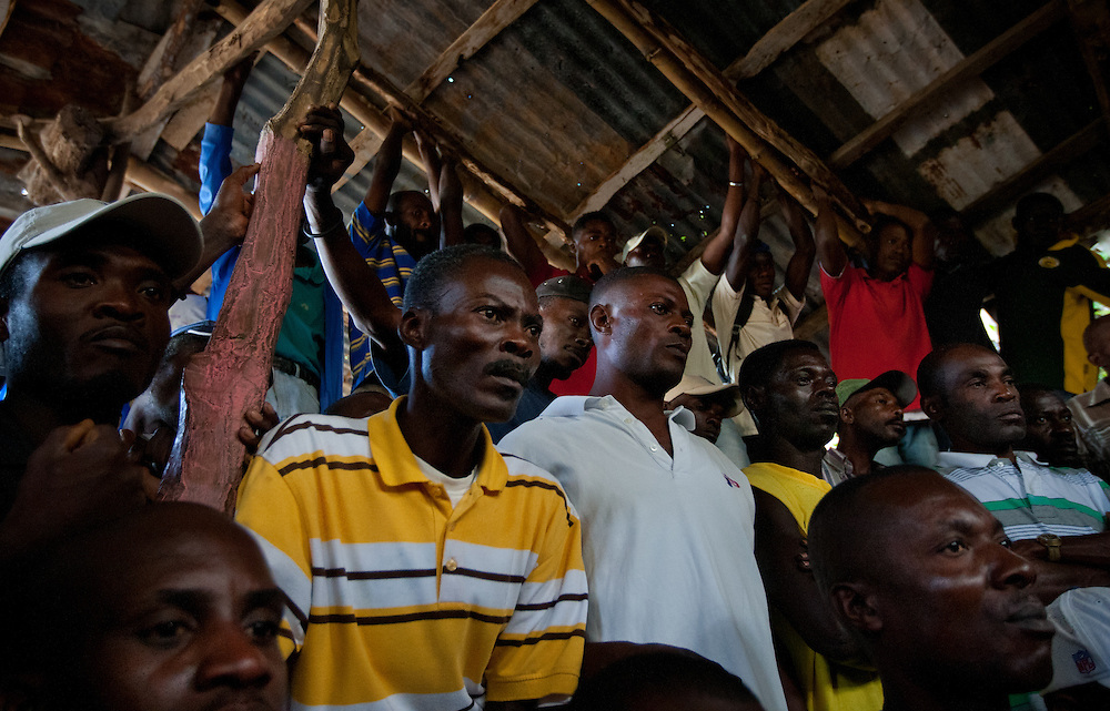 Spectators watch two roosters fight in the middle of the pit.<br /> <br /> Cockfighting or &quot;Cok Kages&quot; is Haiti's national passion.  Many argue that this sport serves as a form of entertainment and distraction where many could release their frustration and aggression in a safe arena.  The sport is legal in Haiti and less vicious since they don't attach blades to their feet. This event usually takes place on Sundays throughout Haiti.