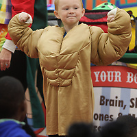 "Braydon Russell, a kindergartener at Parkway Elementary School, flexes his muscles while wearing a muscle suit during a visit from HealthWorks Wednesday morning in Tupelo. Russell was chosen to wear the suit to help illustrate building muscle by eating foods with protien and proper exercise. HealthWorks held a circus themed education class as part of ""Health Week"" that studies the skin, bones and muscles where they did lessons and PE related activities and games Wednesday morning at Parkway in Tupelo."