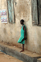Ghana, Accra, 2007. A girl with nothing much to do watches life go by on this Jamestown alley.