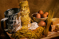 Dried pasta and other pasta ingredients are displayed on a wooden cutting board with a flour sifter, wedges of Romano cheese, and a bowl of brown farm eggs. Pastas pictured include bird's nest pasta, spaghetti noodles, fettuccine, farfalle (bow-tie pasta), and fiori. (Photo by Carmen K. Sisson/Cloudybright)