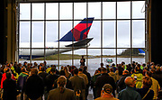 Delta employees, SkyMiles customers and Boeing employees who worked on the 747-400 program, attend a ceremony at the Future of Flight Museum in Everett to honor the airplane that rolled out of the 747 factory in Everett on Sept. 13, 1999. This Delta Air Lines 747 will retire by year end [2017] and is on a farewell tour of the country. The 747 is seen through some giant windows in the background. (Mike Siegel/The Seattle Times)