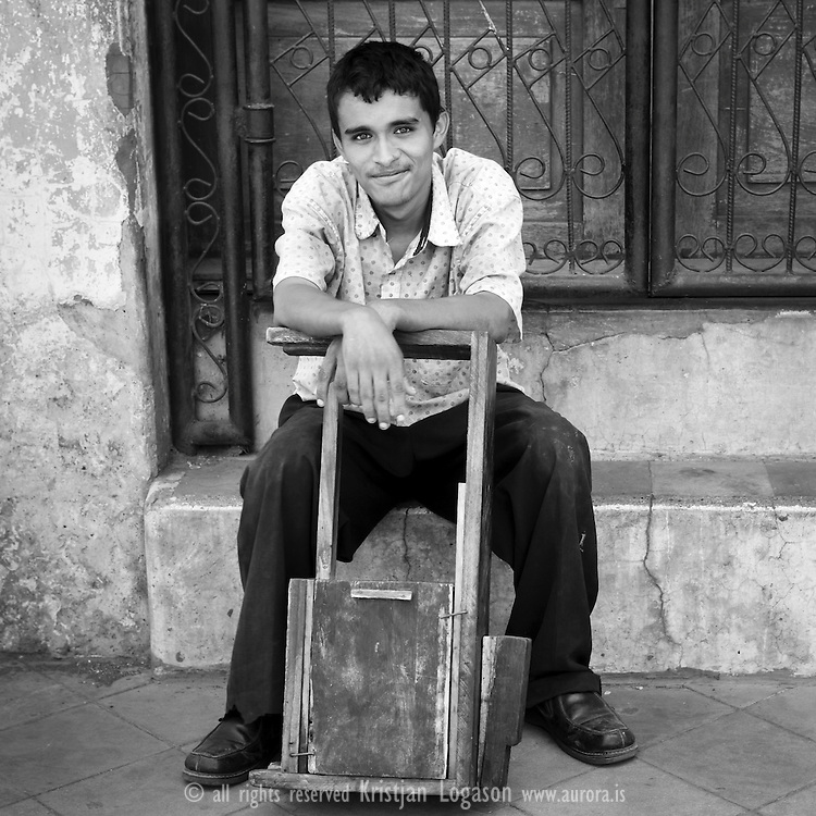 Smiling young man reddy to get your shoe shining in a street in Nicaragua