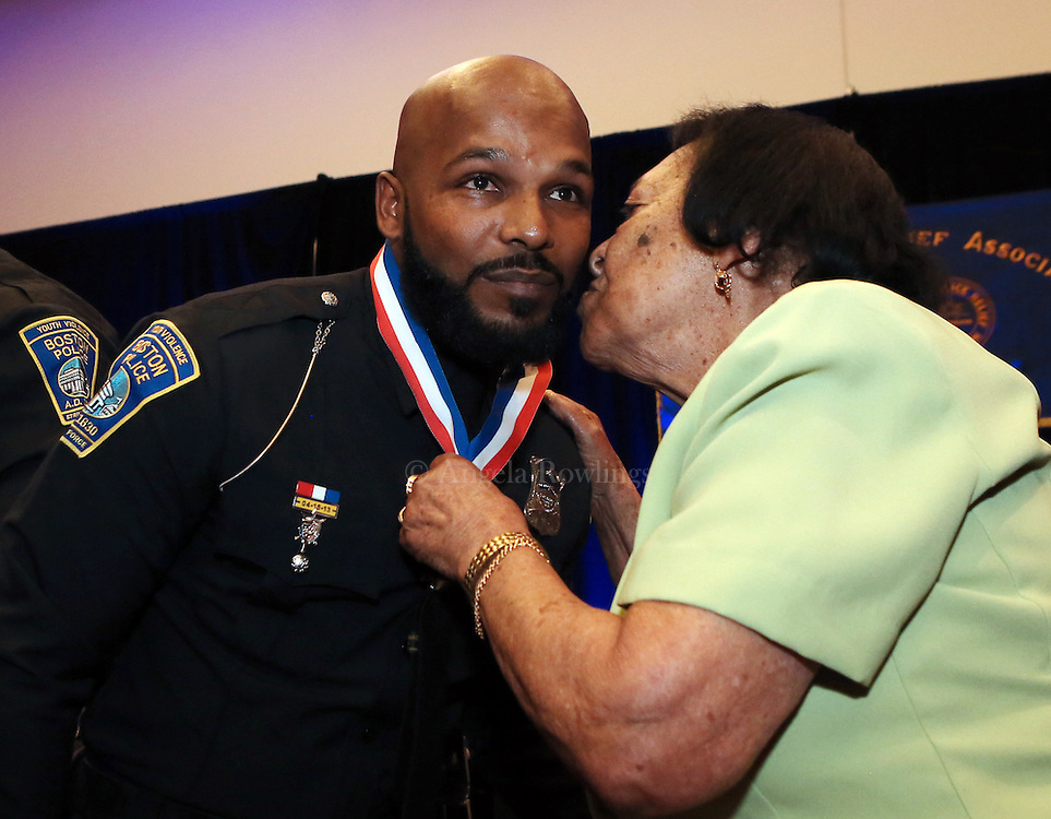 (Boston, MA - 12/6/15) Boston Police Officer Nilton Ramos gets a kiss from his grandmother, Paula DeAndrade, after she presented him with the Department Medal of Honor in Memory of Police Officer Thomas F. Rose during the Boston Police Relief Association 144th annual Ball & Awards Ceremony at the Boston Convention and Exposition Center, Sunday, December 06, 2015. Staff photo by Angela Rowlings.