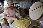 Akbar Zareh, who has worked in a bakery seven days a week since he was a young boy, makes dough in his bakery in Yazd, Iran. (Akbar Zareh is featured in the book What I Eat: Around the World in 80 Diets.) MODEL RELEASED.