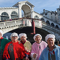 """VENICE, ITALY - JANUARY 06:  Rowers dressed in costume  celebrate next to the Rialto Bridge at the end of the """"Befana"""" Regatta on January 6, 2014 in Venice, Italy. In Italian folklore, Befana is an old woman who delivers gifts to children throughout Italy on the feast of the Epiphany on January 6 in a similar way to Saint Nicholas or Santa Claus.  (Photo by Marco Secchi/Getty Images)"""