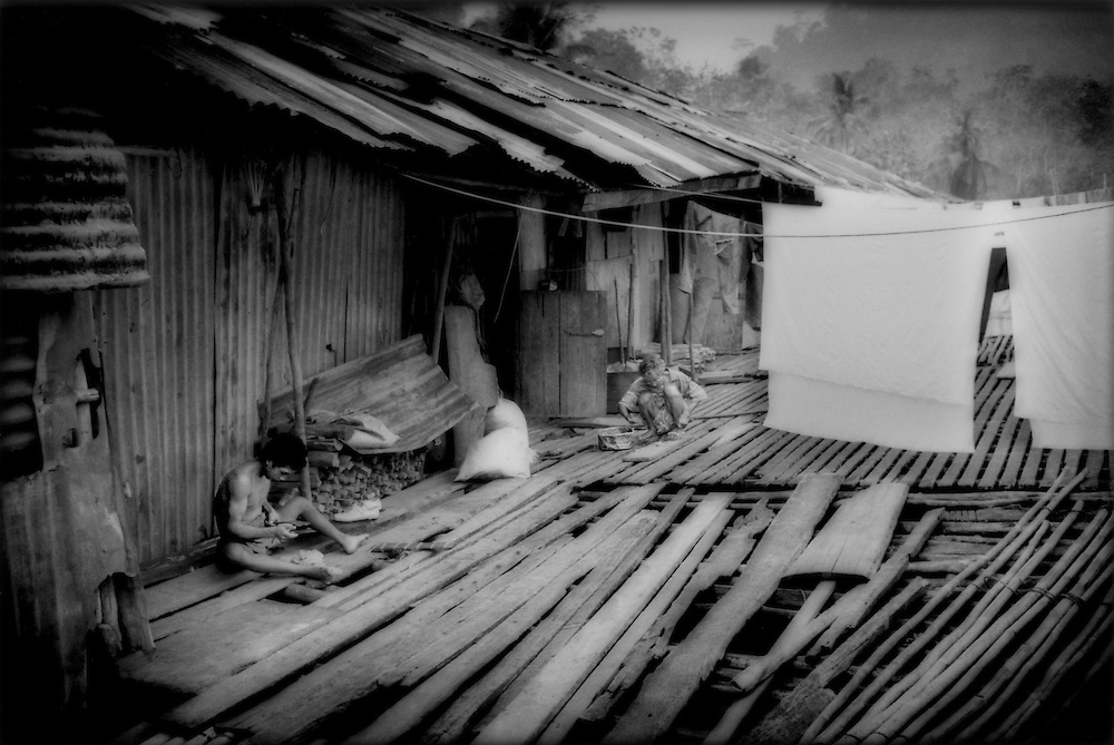 "Iban Dayak residents of Nanga Sumpa working on the platform of the longhouse, Sarawak, Malaysian Borneo.  Maintainance of the longhouse is communal except for this outdoor platform where each family maintains the section in front of their indivivdual ""bilik"" apartment."