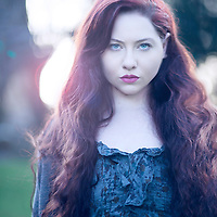 Young woman with long red hair wearing blue dress standing outdoors looking at camera
