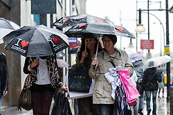© Licensed to London News Pictures. 23/09/2012.  London, UK.  Shoppers on London's Oxford Street endure the heavy rain which is sweeping England today. Photo credit : Richard Isaac/LNP