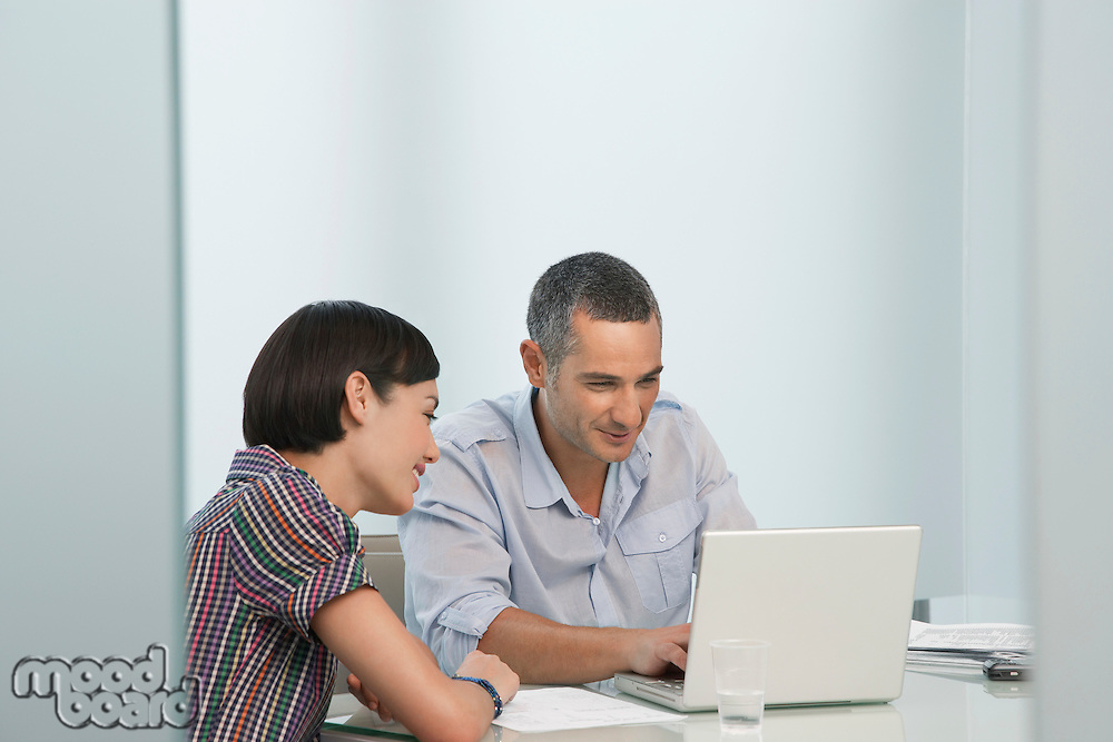 Man and woman working at laptop in office smiling