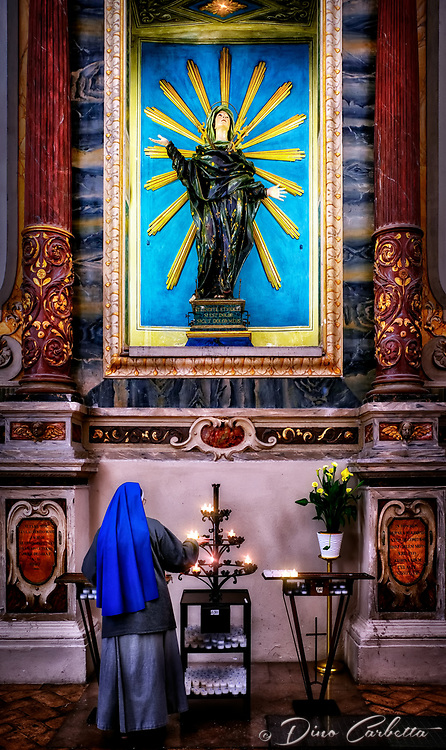 """""""Our Lady of Sorrows - Cathedral of San Rufino, Assisi""""…<br /> <br /> The first time I visited the Cathedral, I was laboriously working my way up the Assisi mountain top, of which the Cathedral of San Rufino is the last church. Upon my most recent Pilgrimage, I learned that taking a taxi to Rocco Maggiore at the very top and working downward is much less strenuous. Although every building in Assisi celebrates Saint Francis, the city's cathedral is dedicated to San Rufino. It's named for Assisi's patron saint, a former 3rd-century bishop, and martyr. After converting Assisi to Christianity, he was killed by drowning in a nearby river. The cathedral has been a very important aspect of the history of the Franciscan order. It was here that Saint Francis, Saint Clare, and many of their original disciples were baptized. Hearing Francis preaching in this church in 1209, Saint Clare became deeply touched by his message and realized her calling. In 1228, here for the canonization of Saint Francis, Pope Gregory IX consecrated the high altar. A humorous story of the relics of Saint Rufino remaining in this ancient church before it was consecrated as a Cathedral is part of history. The townspeople fought for the saint's body with the current Bishop Ugone, who wanted to move it to the Cathedral of Santa Maria Maggiore. The citizens took a position against the move and started a real """"tug of war"""" with the saint's coffin. The sixty Bishops' men were beaten by only seven Assisi citizens. The victory was seen as miraculous, even by Ugone, who then decided to renovate the small Basilica, which eventually became the Cathedral for Assisi. Altare dell' Addolorata consists of this dramatic statue of the Madonna Addolorata from 1672. Upon lighting candles for friends and family, a Franciscan Sister unknowingly posed in reflection completing the reverent presentation."""