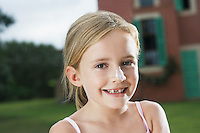 Portrait of girl (5-6) with sunscreen on nose
