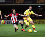 Milton Keynes Dons midfielder Samir Carruthers trying to get away from Brentford midfielder Sam Saunders during the Sky Bet Championship match between Brentford and Milton Keynes Dons at Griffin Park, London, England on 5 December 2015. Photo by Matthew Redman.