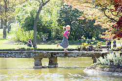 © Licensed to London News Pictures. 16/04/2014. Cliveden, UK A  girl runs across stepping stones in the water garden.  People enjoy the   sunshine at Cliveden in Buckinghamshire today 16th April 2014. Photo credit : Stephen Simpson/LNP
