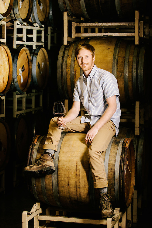 Marc Myers winemaker for The Four Graces in Dundee in Oregon sitting on oak barrels