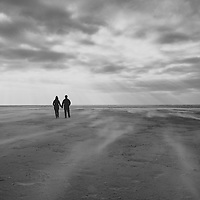 Man and woman walking on a beach holding hands