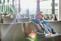 Mature businessman sitting and sleeping with his pillow while waiting for boarding in airport