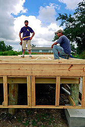 23 August 2013. Lower 9th Ward, New Orleans, Louisiana.<br /> Katrina 8 years later. In a tale of two cities, the hardest hit neighbourhoods struggle to revitalize and return. L/R; Josh Gillikin and David Rosa, contractors working for Brimmer Construction Services begin the extensive process of rebuilding a formerly derelict house. Many half finished or blighted properties and vacant overgrown lots remain dotted throughout the landscape. Residents who have returned complain of limited services, infrequent police patrols, high crime rates, rampant mosquitos and uncontrolled vermin. <br /> Photo; Charlie Varley