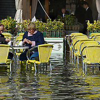 VENICE, ITALY - NOVEMBER 05:  A couple has drinksat a Cafe in Saint Mark's Square during today Acqua Alta on November 5, 2013 in Venice, Italy. The high tide, or acqua alta as it is locally known, is a natural event most commonly affecting the city during Autumn and Winter.  (Photo by Marco Secchi/Getty Images)